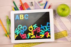 Stock Illustration of Composite image of digital tablet on students desk