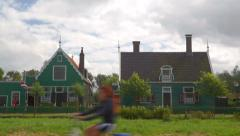 Tourists on bicycles passing ancient houses at the Zaanse Schans - stock footage