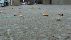 Cigarette Butts On The Sidewalk By The Riverside Stock Footage