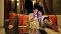Couple watching funny things on smartphone and table at home HD - stock footage