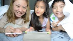 Asian mother with your son and daughter play on tablet on the bed . Stock Footage