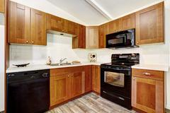 kitchen cabinets with black appliances - stock photo