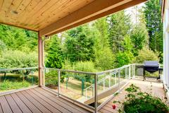 wooden walkout deck with glass railing - stock photo