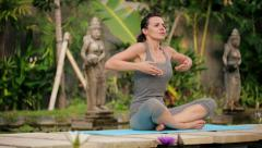 Attractive woman doing breathing exercise in exotic garden HD Stock Footage