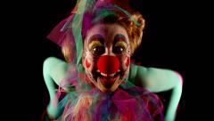 Female clown is making grimaces in front of  black background Stock Footage