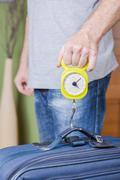 Man checking luggage weight with steelyard balance - stock photo