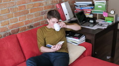 Young man reading book and drinking beverage on red sofa Stock Footage