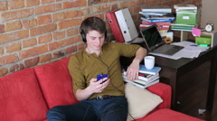 Student listening music on headphones and sitting on red sofa Stock Footage