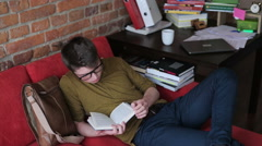 Student finish reading book and taking a nap on red sofa Stock Footage