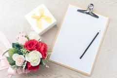 wooden clipboard attach planning paper with pencil beside rose bouquet ,gift  - stock photo