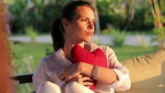 Sad, heartbroken woman with heart shape cushion sitting in gazebo HD Stock Footage