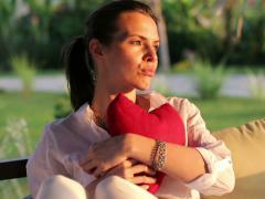 Sad, heartbroken woman with heart shape cushion sitting in gazebo NTSC Stock Footage