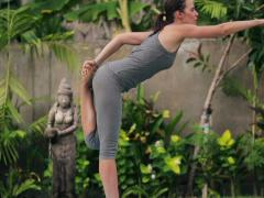 Young woman exercising, doing yoga pose in exotic garden NTSC Stock Footage