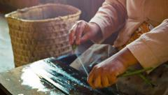 Woman makes yarn from the juice of the lotus. old-fashioned way. burma, inle Stock Footage