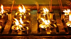 Oil lamps in a buddhist temple at night. myanmar, yangon Stock Footage