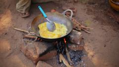 Local man prepares an omelet on a fire in the open air. burma bagan Stock Footage
