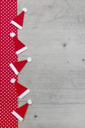 christmas hats, red and white polka dot fabric on grey wooden background - stock photo