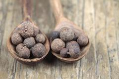 Allspice on wooden spoons Stock Photos