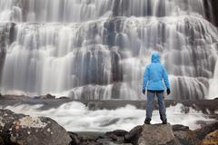 hiker in front of the dynjandi waterfall, fjallfoss, west fjords, iceland, eu - stock photo