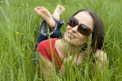 young woman, 30, relaxed, lying on a lawn in spring - stock photo