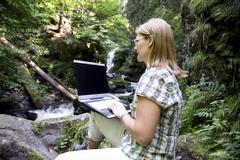 woman, mid 40, surfing in the internet outdoors, ravennaschlucht gorge, hinte - stock photo