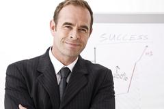 manager smiling, standing in front of a flipchart - stock photo
