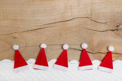 red christmas hats on wooden background for a greeting card - stock photo