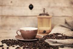 Old aged still life on coffee beans, cup and coffee grinder Stock Photos