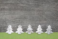 wooden christmas trees with green fabric on grey wooden background - stock photo