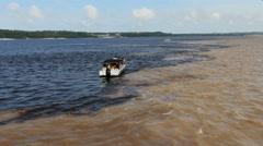 Amazon small boat at the meeting of waters  Stock Footage