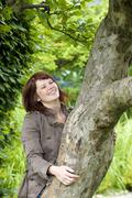 happy woman, 25 +, hugging a tree - stock photo