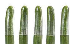 Condoms on cucumbers, contraception concept Stock Photos