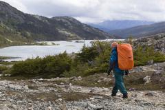 female hiker, backpacker walking in alpine landscape, deep lake behind, chilk - stock photo