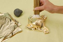 gilding with gold leaf and gilding brush - stock photo