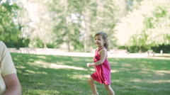 Beautiful little girl plays with her family in park Stock Footage