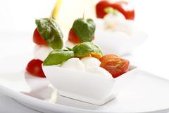 Stock Photo of tomato-mozarella sticks with basil in a bowl
