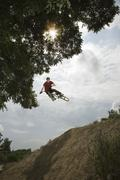 A BMX rider in mid-air at the top of a mud slope Stock Photos