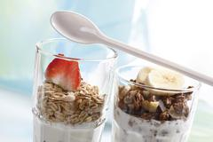 muesli and chocolate muesli with yoghurt and in a small glass jar, sliced ban - stock photo