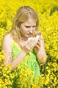 Young blond girl with an allergy standing in a field of rape Stock Photos