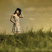 young woman with a flowery summer dress and large hat is standing in a meadow - stock photo