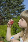 Little girl, 7 years old, blowing soap bubbles Stock Photos