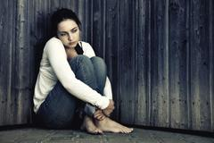 Stock Photo of young sad woman in jeans is sitting in a corner with her back to the wall