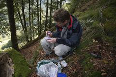 man lifting a geocache, near hofsgrund in the black forest, germany, europe - stock photo