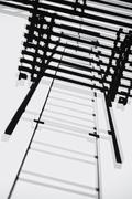 Looking up fire escape ladder Stock Photos