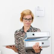 young woman eyeing office binders with a grimace - stock photo