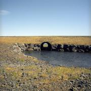 A culvert pipe carrying water for a stream under a field Stock Photos