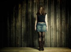 young woman with jeans skirt and boots in front of a wooden wall - stock photo