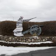 A covered statue next to an old cannon Stock Photos