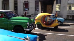 Funny yellow scooter taxi between the classic cars in Havana, Cuba - stock footage