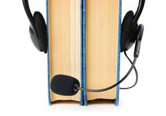 headphones with a microphone and a stack of books isolated on white backgroun - stock photo
